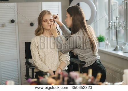 Makeup Artist Work In Her Beauty Studio. Portrait Of Woman Applying By Professional Make Up Master.