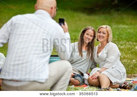 Rear view of man taking picture of friends with cell phone
