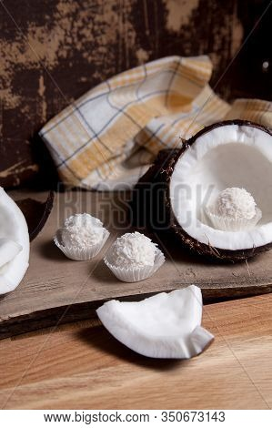 Coconut With White Pulp And White Candies On Wooden Background..