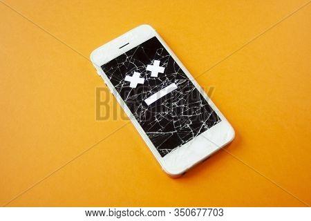 Broken Smartphone With Cracked Destroyed Screen On Orange Background With Sad Smile. Broken Phone Se