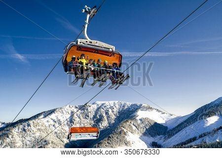 Demanovska Dolina, Slovakia - February 8: Skiers Sitting On Ski Lift Chair  In Ski Resort Jasna On F