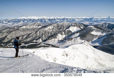 Skier Freerider On Top Of The Hill Chopok At Low Tatras. High Tatras Mountains At Background