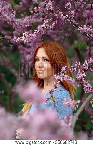 Beautiful Smilling Redhead Woman In Spring Time Blossom Cherrytrees Garden.