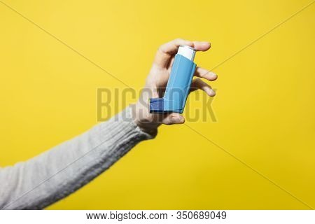 Close-up Of Male Hand Holding Asthmatic Inhalator On Yellow Background.