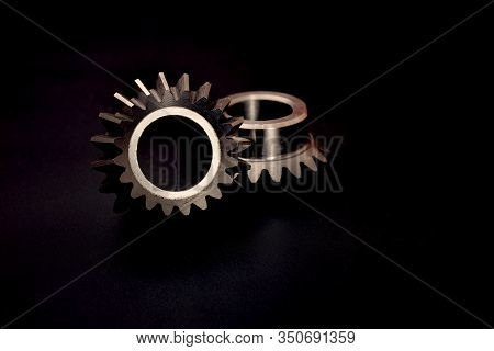 Two Bevel Gears On A Black Background, Advertising Of Manufactured Products At A Gear-cutting Enterp