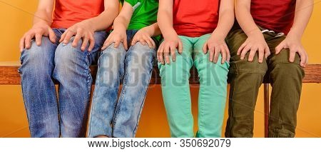 Four Children In Bright And Colorful Clothes Are Sitting With Their Legs Dangling And Hands On Their