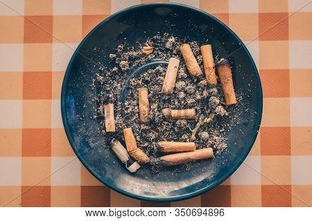 Dirty Blue Ashtray Full Of Cigarettes And Marijuana Butts On Orange Background