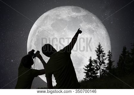 Silhouettes Of People Observing Stars In Night Sky. Moon In Background.