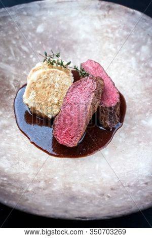 Fried dry aged venison tenderloin fillet medallion steak natural with bread dumpling and spicy gravy sauce as closeup on a modern design plate