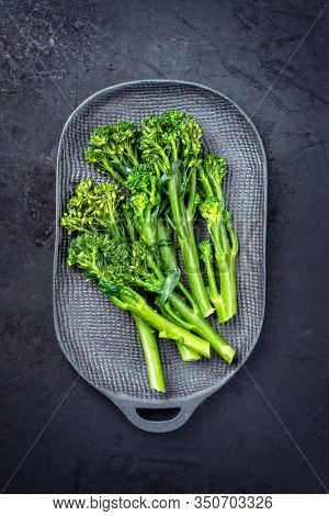 Fresh rapini broccoli rabe as top view on a black plate with copy space