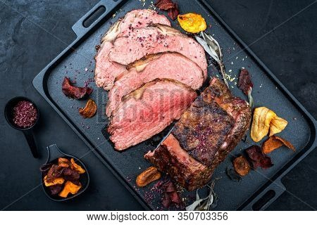 Traditional Commonwealth Sunday roast with sliced cold cuts roast beef with vegetable chips and herbs as top view on a modern design tray