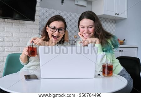 Relations Between Mother And Teen Daughter, Parent And Teenager Sitting At Home In Kitchen Drinking