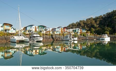 Waterfront Maritime Marina/dock With Boats In Tropical Water With Blue Sky Backdrop. Safe Haven And