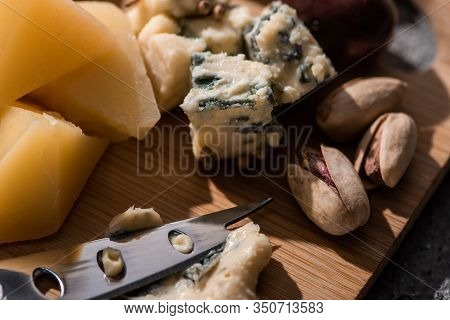 Selective Focus Of Dorblu Pressed By Knife Next To Pieces Of Grana Padano And Pistachios On Cutting