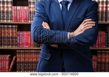 Portrait Of Confident Attorney Standing Arms Crossed Against Bookshelf In Office