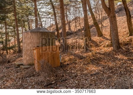 Water Storage Tank In Wooded Mountainside Park Under Tall Evergreen Trees,