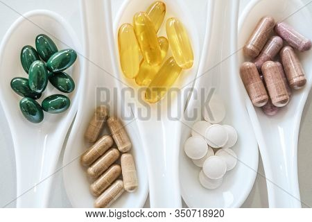 Top View Of Natural Vitamin Supplement On White Spoon As Frame Of Marble Texture Background. Healthy