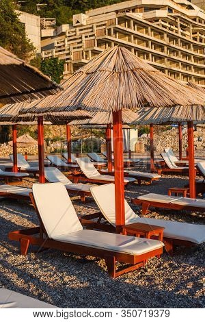 Chaise Longues With Umbrellas On The Sea Beach During Sunset. Montenegro, Summer, Tivat City