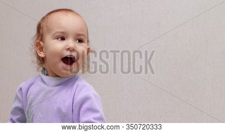 Banner, Copy Space. Toddler With Open Mouth. A Little Girl In A Purple Jumper Screams Joyfully. Beau