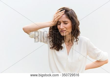 Upset Young Woman With Headache. Sad Caucasian Woman With Migraine Holding Hand On Head. Headache, M