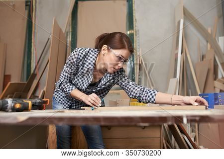 Woman woodworker with wooden board behind workbench