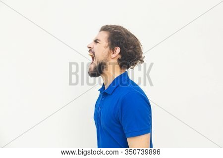 Side View Of Angry Young Man Screaming. Angry Man Screaming Loud With Wide Open Mouth. Negative Emot