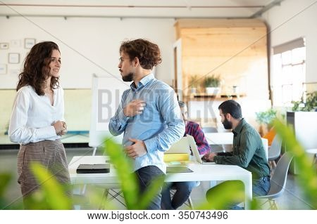 Side View Of Smiling Woman Talking With Colleague In Eyeglasses. Two Coworkers Communicating In Open