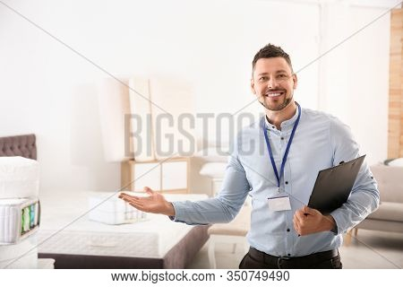 Happy Salesman With Clipboard In Mattress Store. Space For Text