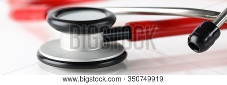 Close-up Of Red Medical Stethoscope Lying On Clinical Table. Cardiological Tool For Patients Diagnos