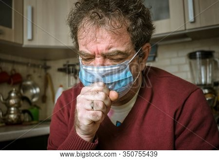 Adult man in a medical mask coughs in a living room at home. Real people everyday life