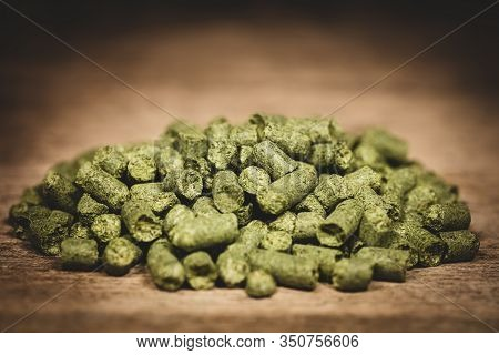 Dried Green Hop Pellets On Wooden Ground, Ingredient For A Brewery, Beer Company Or Plant