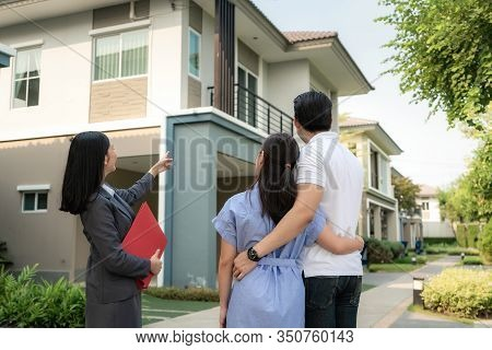 Asian Woman Real Estate Broker Agent Showing A House Project Detail In Her File To The Young Asian C