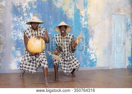 People In Traditional African Costumes Playing Jembe Drums