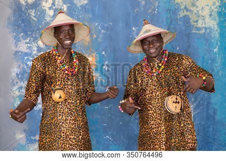 Handsome African Men In Traditional Fulani Hats And Colorful Clothes Smiling And Looking At Camera