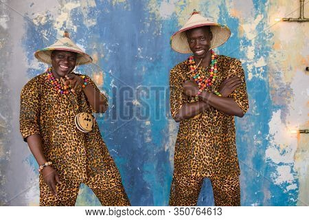 Handsome African Men In Traditional Fulani Hats And Colorful Posing At Studio.