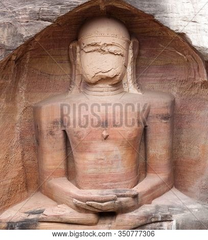 Ancient Giant Jain Statue In Lotus Position Carved Out Of Rock Near Gwalior Fort. Gopachal Rock Cut