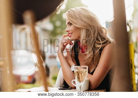 Smiling Blonde Girl Sitting On Date At The Table With Cup Of Coffee And Glass Of Wine On It. Outdoor