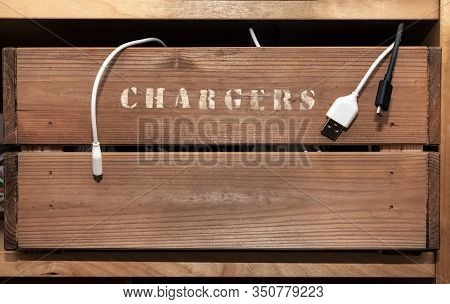 An Old Vintage Style Crate On A Shelf With The Word Chargers Hand Painted On The Side. Cables Hang O