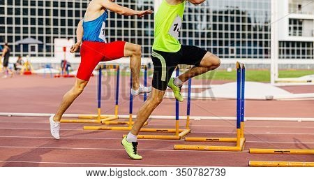 Male Athletes Run Hurdles At Stadium In Athletics Competition