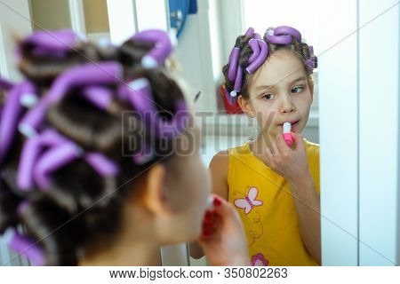 A Little Girl Pretends To Be An Adult Woman With Curlers In Her Hair Paints Her Lips With Lipstick L
