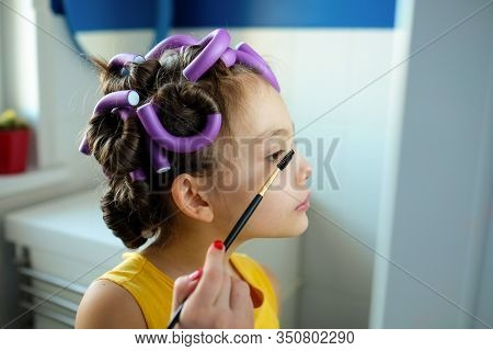 A Little Girl Pretends To Be An Adult Woman With Curlers In Her Hair Holds Eyebrow Brush Looks In Th