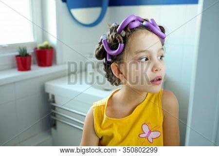 A Little Girl Pretends To Be An Adult Woman Or Her Mommy With Curlers In Her Hair Looks In The Mirro