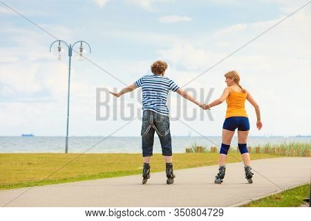 Holidays, Active People And Friendship Concept. Young Fit Couple On Roller Skates Riding Outdoors On
