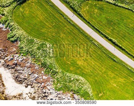 Aerial Top Down View Of Country Road Through Green Land Field Along Sand Beach Seashore, Gimsoya Isl
