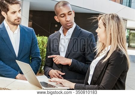 Professionals Instructing Junior Employee. Woman In Office Suit Listening To Speaking And Gesturing