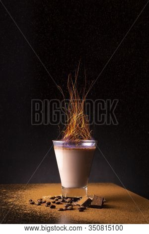 Irish Cream Coffee Cocktail On Fire Served In A Cocktail Glass On A Bar Counter; Burning Irish Cream