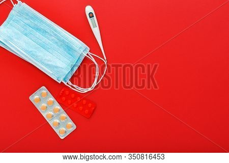 Medical Mask, Medical Protective Mask, Pills Syringes Thermometer On Red Background Copy Space. Heal