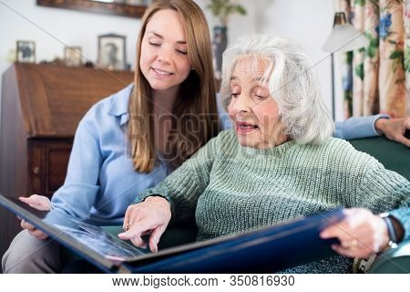 Grandmother Looking At Photo Album With Adult Granddaughter