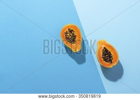 Ripe Papaya Fruit Cut In Half On Duotone Blue Background, In Harsh Light. Above View Of Papaya Fruit
