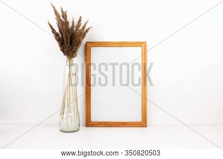Wooden Empty Frame Mockup With Copy Space, Trendy Dry Flowers In Glass Bottle On White Background. I
